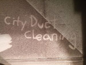City Duct Cleaning name written in the dust inside a large air duct.