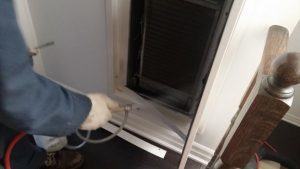 Applying duct sealer to the interior liner in a fan coil unit.